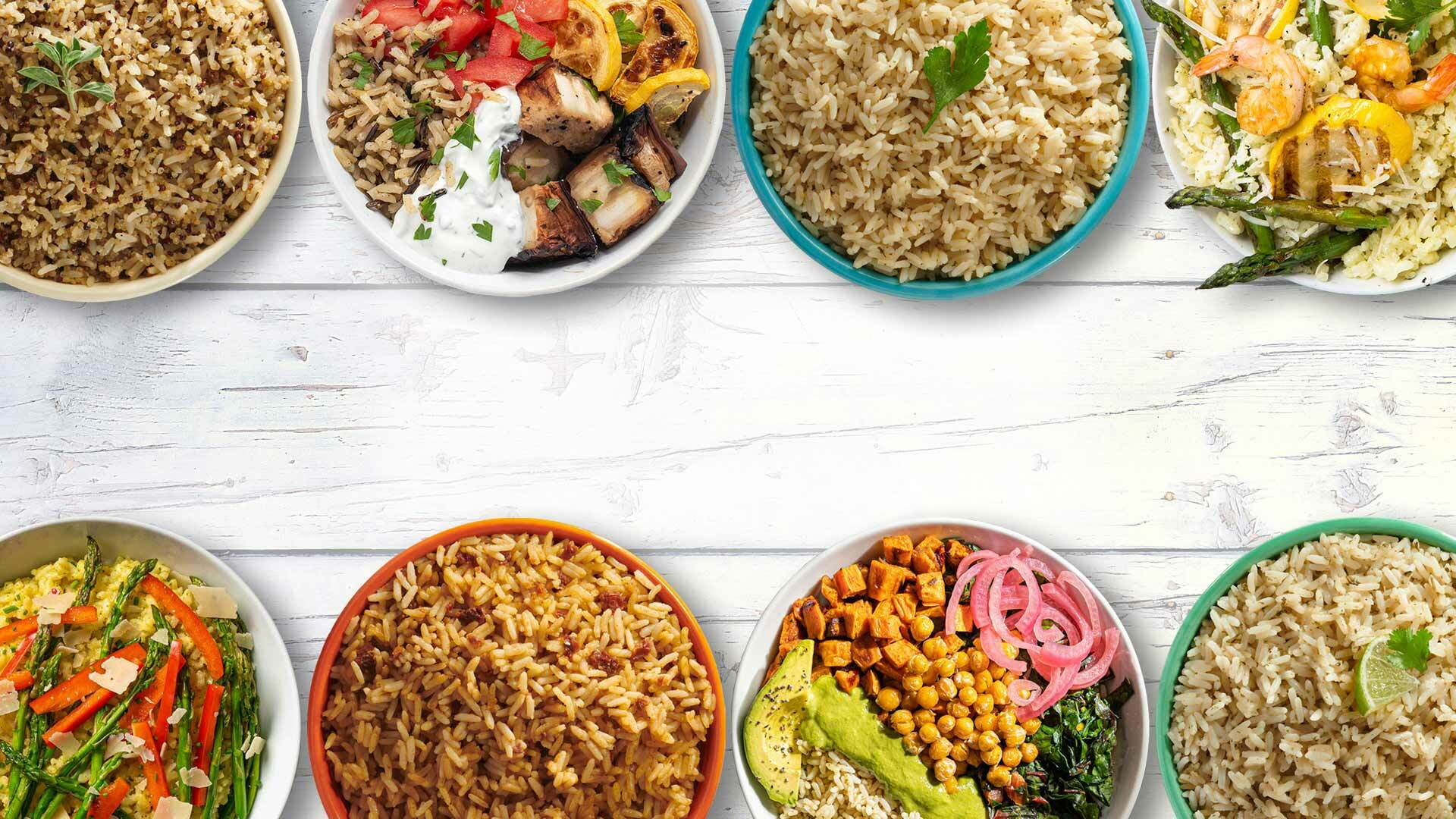 Bowls of cooked rice dishes on white table