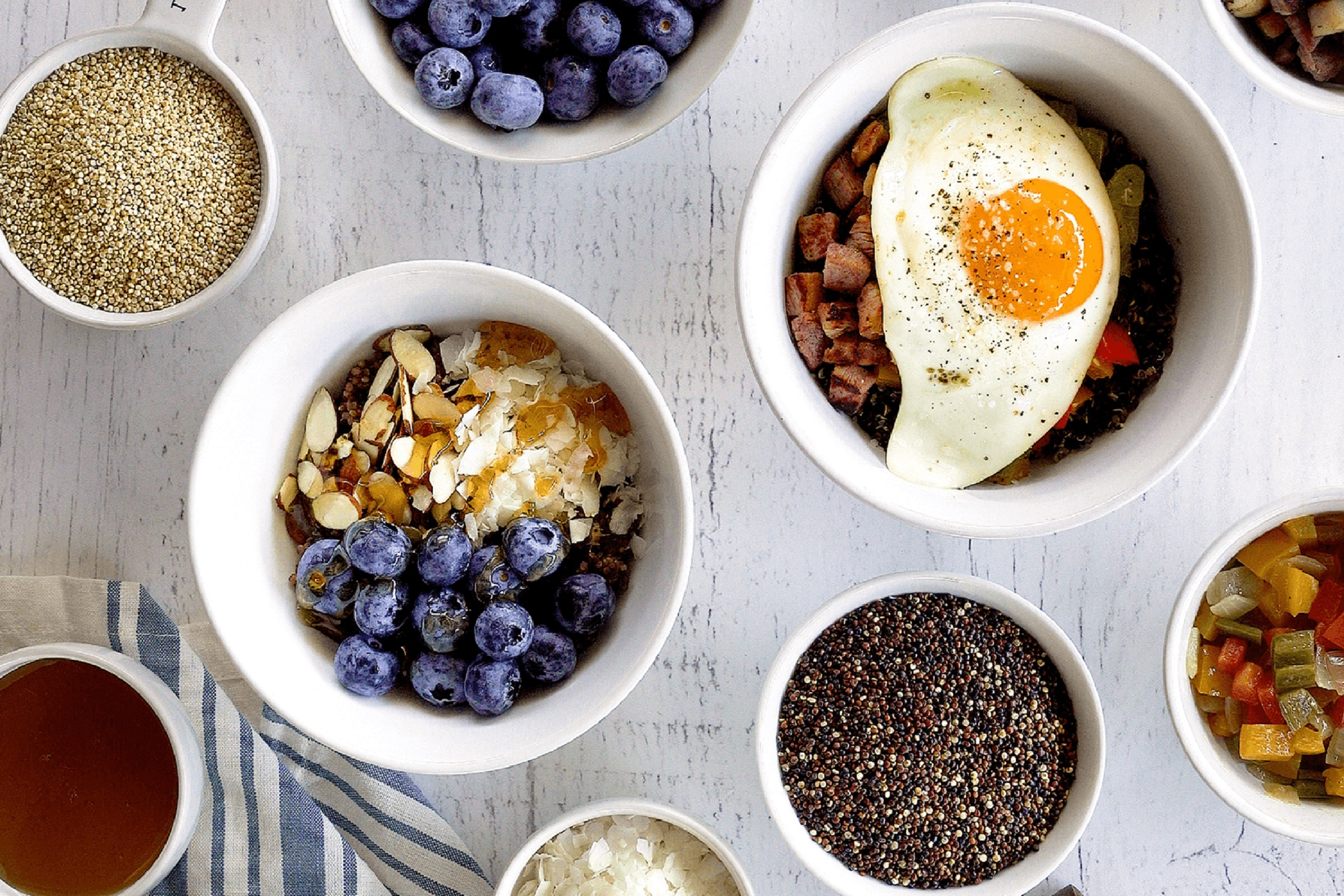 Lundberg Organic Antique White and Tri-Color Blend Quinoa are shown with sweet and savory breakfast bowls.
