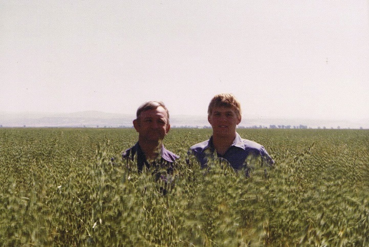 Harlan and Bryce Lundberg, father and son, stand in a field of cover crops circa the 1980s.
