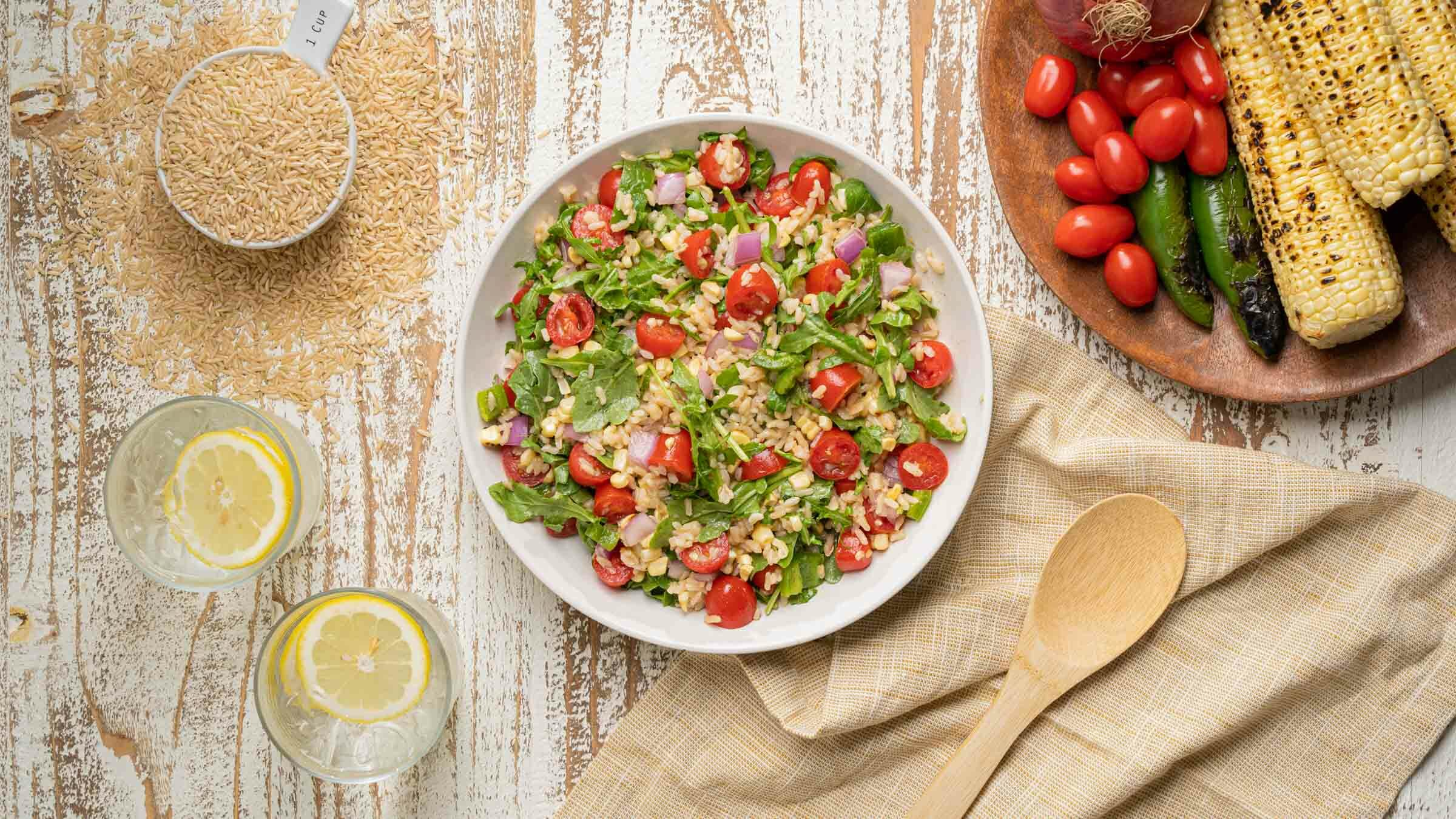 Summer Salad with corn, rice, onions, tomatoes and arugula in bowl.
