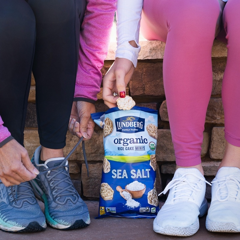 Two women tie their shoes and enjoy Sea Salt Rice Cake Minis before their workout.